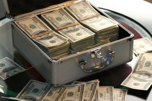A suitcase with dollar bills in it and around it.