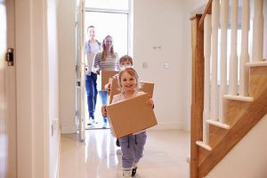 Two children and their parents walking through the front door of their family home holding boxes