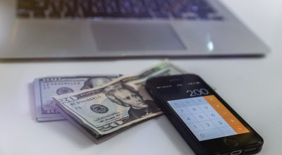 A cell phone, dollar bills and a laptop on a table