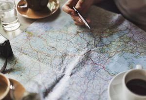 A cup of coffee and hand holding a pen over a map, doing research on hiring a cheap moving company from Florida