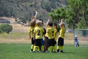 Kids playing soccer in jerseys