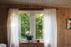Windoes such as this window with drapes between wooden walls should always be under close scrutiny during estate inspection.