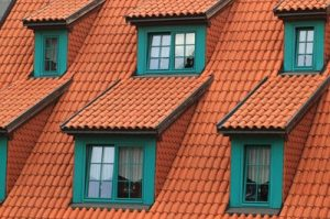 Roofs such as this tiled orange roof with windows leading to the attic should always be checked during estate inspection.