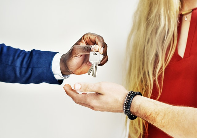 A man giving keys to his tenants.