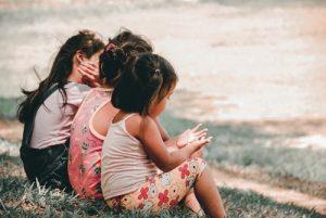 Three girls sitting on grass slope