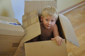 child in box - What to Unpack First in Your New Home?