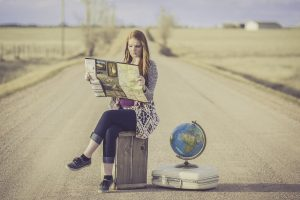 A woman sitting on a suitcase with a globe next to her. What the right moving outfit is depends on where you are moving to.
