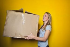 One of the reasons to rent short-term storage is changing your place of residence - woman holding a box