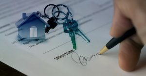 An image of a small house on a keychain with keys and a piece of paper being signed showing the process of buying a property