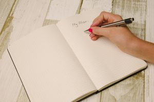 Woman holding a pencil and writing a plan in the notebook
