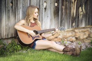 A girl sitting on grass and playing the guitar - an ordinary view you will see after moving to Nashville