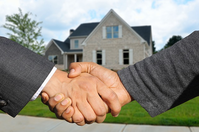 Two people shaking hands in front of a house