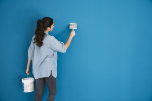girl painting wall, a good way to quickly adjust after moving