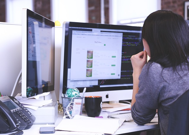 A businesswoman working on a computer in an office.