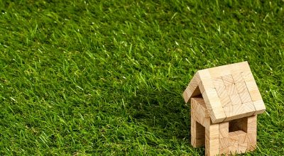 A small wooden toy house on a mowed lawn, representing ways to save money when buying a house.