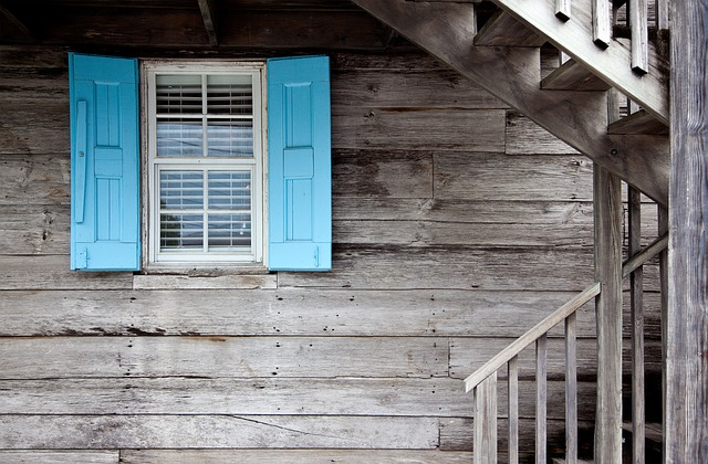 A run-down wooden house, with blue window shutters.