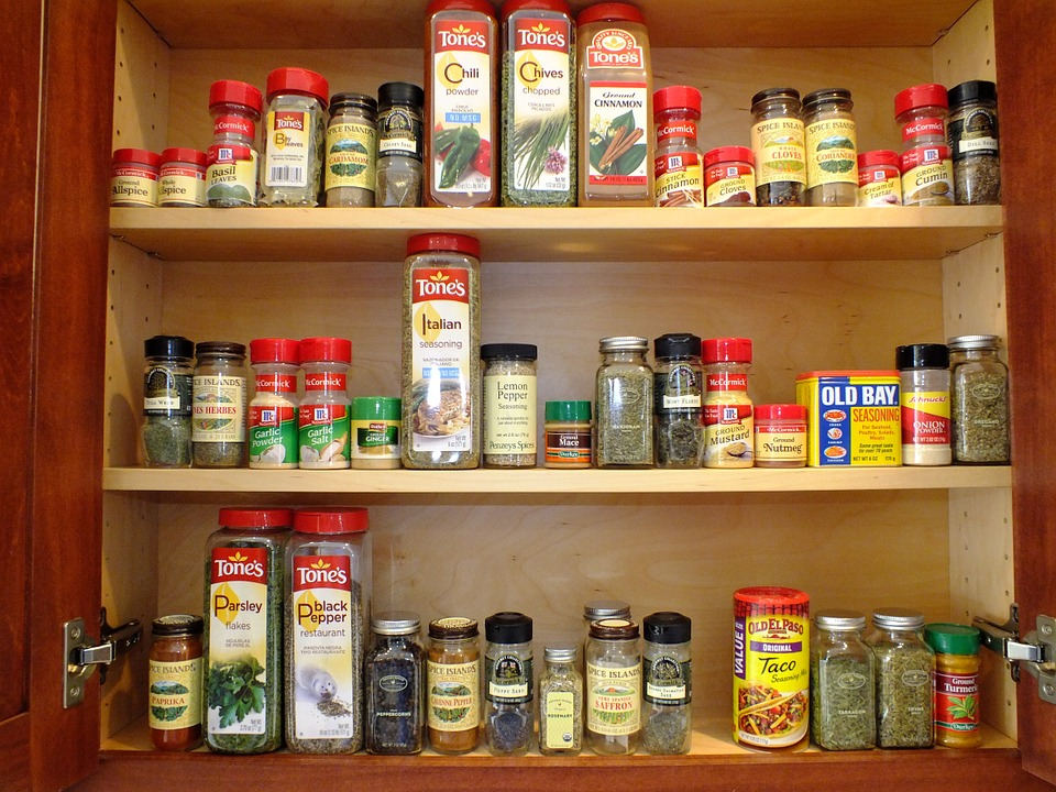Kitchen cabinet filled with different spices.
