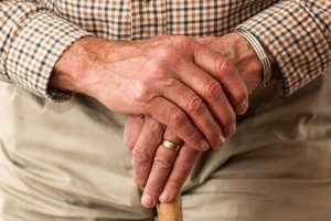 An elderly man leaning on a cane.