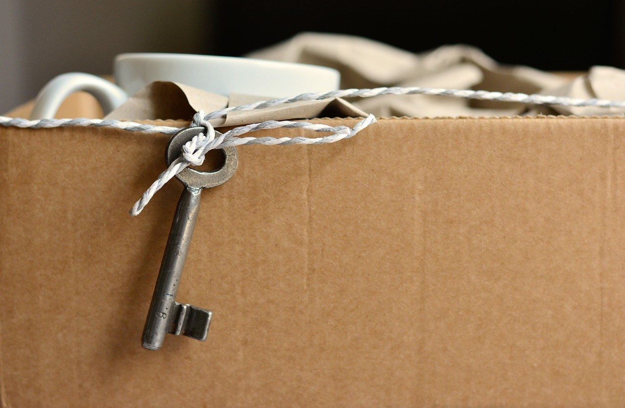 A cardboard box full of packed things, and a key hanging outside the box.