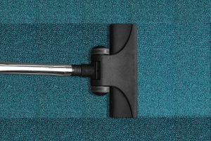 A vacuum cleaner on a blue carpet.
