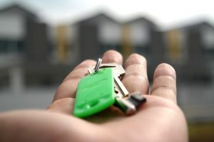 A person holding a house key with a green key chain .