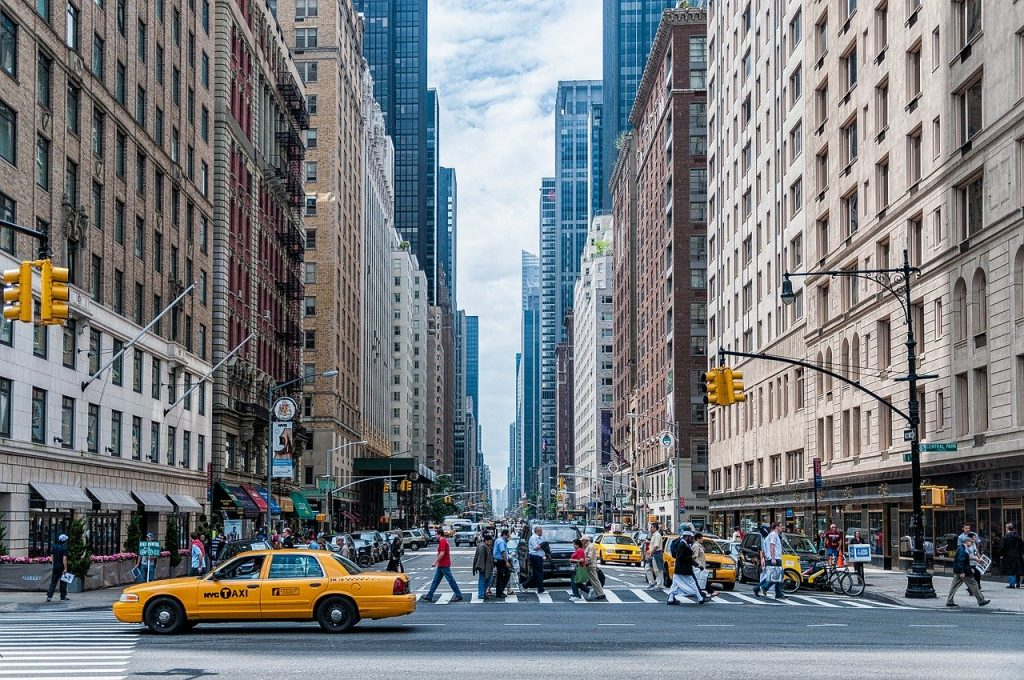 Manhattan street with tall buildings and a yellow cab.