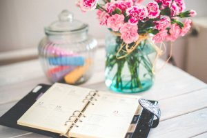 Some flowers and a planner which can be helpful to organize your long-distance moving.