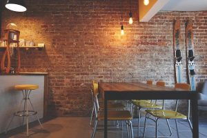 The interior of a cozy dining room with brick walls.