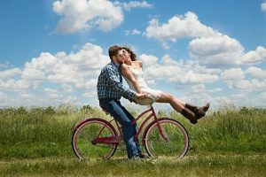 A man and a woman on a bicycle in the nature.