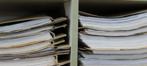 Piles of documents on a shelf - something you will have to deal with when involved in the home buying process in Canada.