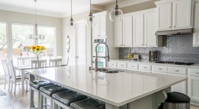 There is a kitchen table, some chairs, some white cupboards and other, maybe upgraded, kitchen appliances.
