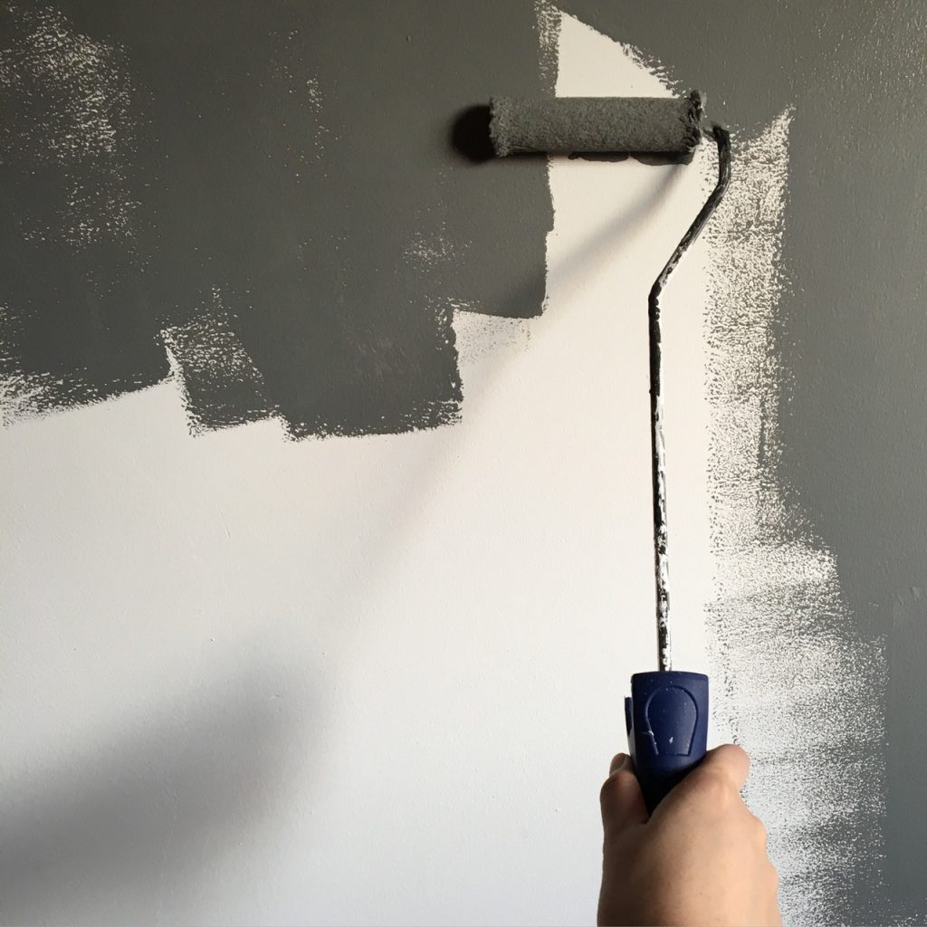 A person painting with a paint roller symbolizing the choice you have to renovate your property before selling it.