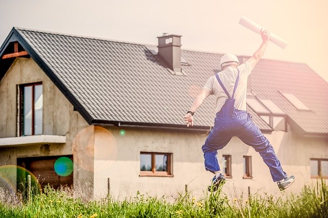 A builder jumping with happiness in front of a house.