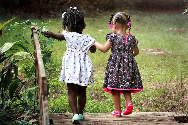 Two small girls, holding hands, living in a great place for raising kids is one of the benefits of starting over in Niles.