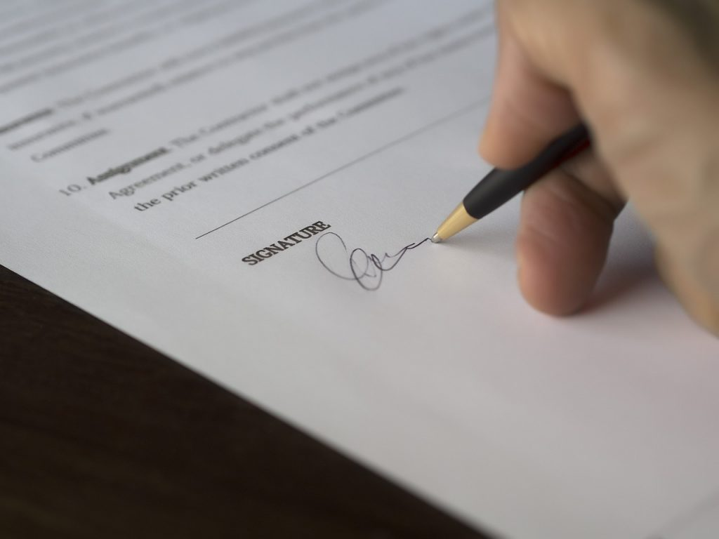 A person signing a document after buying a property in Canada.