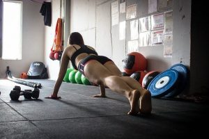 A woman doing a plank in her home gym.