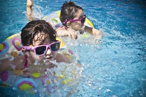 Kids in a pool wearing safety equipment to avoid mistakes when purchasing a pool.