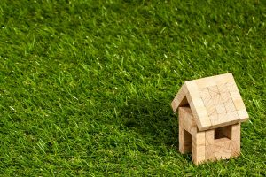 A small wodden model house on the grass.