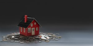 A small model house on a pile of coins.