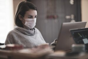 A woman with a mask working at a computer after redesigning the office space for coronavirus safety.