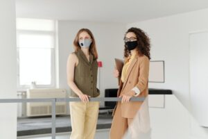 Two business women with masks standing at the office