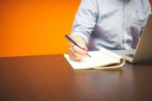 The person takes notes on the elements of the commercial lease agreement