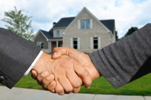 A handshake of a client and a reliable real estate agent in front of a house