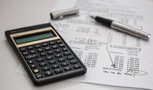 A calculator and a pice of paper to calculate the costs of buying a house in Hong Kong