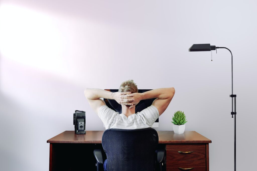 A man sitting in front of his computer thinking about Toronto commercial real estate investment.