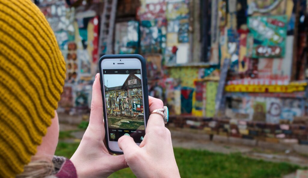 Girl taking a photo of street art after renting an apartment in Detroit