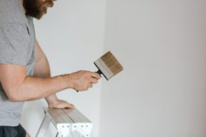 A man on a ladder doing one of the easy remodeling projects - painting the walls.