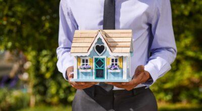 A man holding a little house