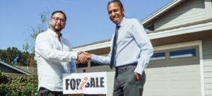 Two men shaking hands above for sale sign