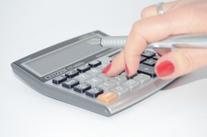 A woman using a calculator to determine the warehouse space and storage capacity.